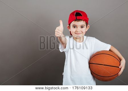 Cheerful little boy in cap holding basketball ball and showing thumbs up over grey background