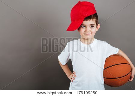 Cute little boy in red cap holding basketball ball over grey background