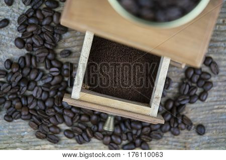 Grinder and coffee beans viewed from above with focus to the open drawer showing the freshly ground powder ready to percolate for coffee
