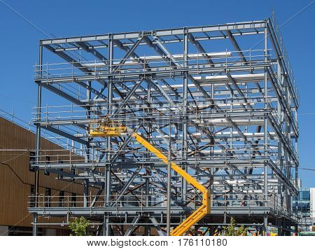 New commercial building construction with yellow crane lifting needed materials