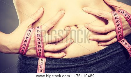 Getting rid of belly fat diet weight loss or gain concept. Woman touching stomach holding measuring tape
