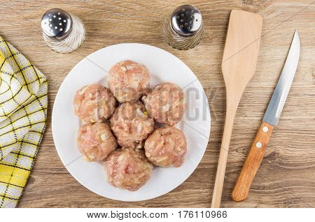 Raw Meatballs In Plate, Spatula, Salt, Peeper And Knife