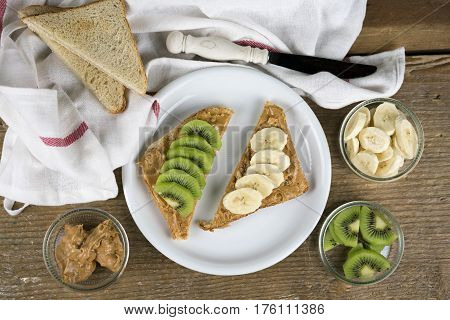 Open peanut butter and fresh fruit sandwiches topped with sliced kiwifruit and banana viewed from above with ingredients