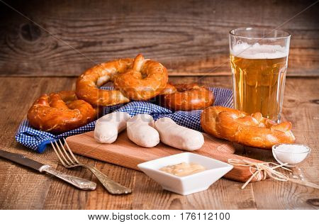 Bavarian pretzels with wurstel and beer on wooden table.