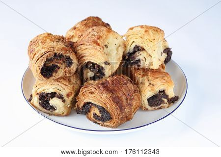 Sweet rolls with poppy seeds on a white porcelain plate with a blue rim and on a light blue surface