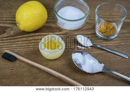DIY toothpaste with ingredients coconut oil lemon turmeric baking soda Xylitol and bamboo toothbrush