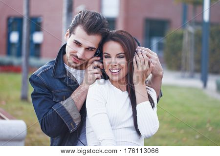 Young caucasian couple listening music by headphones outdoor