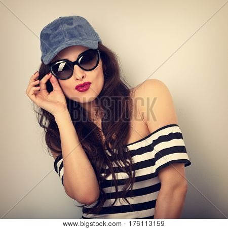 Happy Enjoyment Grimacing Young Woman In Sunglasses And Blue Baseball Cap Posing And Looking In Stri