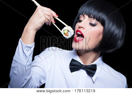 Beautiful woman in wig and red lips eating sushi isolated on black