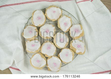 Batch of freshly baked homemade cookies on a wire tray in the kitchen topped with white icing and little pink candy hearts for Valentines or an anniversary
