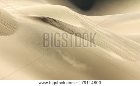 Big wandering sand dune with trails of dust on a windy day in desert or beach. Sand dune texture in african desert.