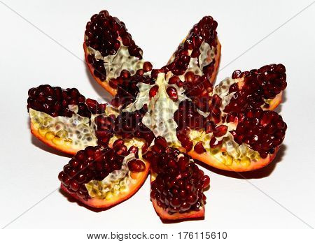 Fruit on a white background. A beautifully opened garnet similar to a flower.