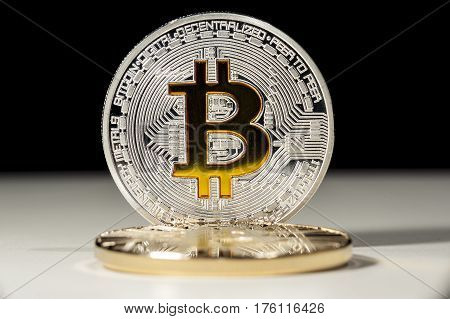 Shining metal BTC bitcoin coins on black and white background.