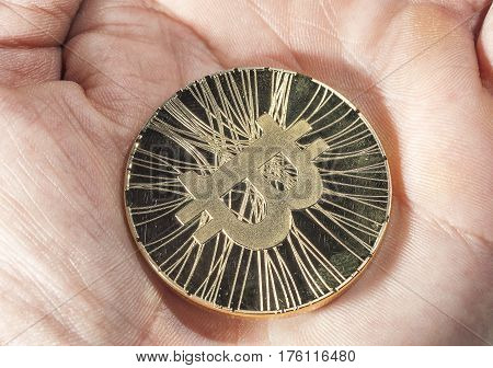 Shining gold metal BTC bitcoin coin lying on human hand.
