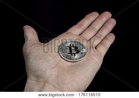Shining silver and gold metal BTC bitcoin coin lying on hand on black background.
