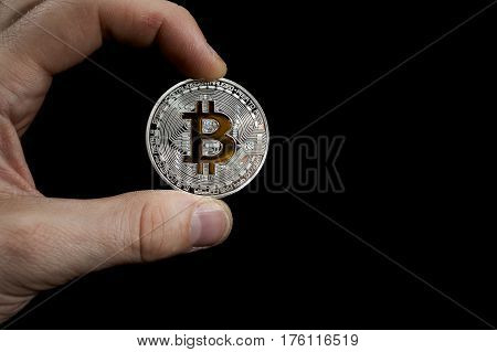 Shining silver and gold metal BTC bitcoin coin holded in hand on black background.