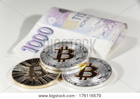 Shining metal gold and silver Bitcoin coins on Czech thousand crowns bank notes