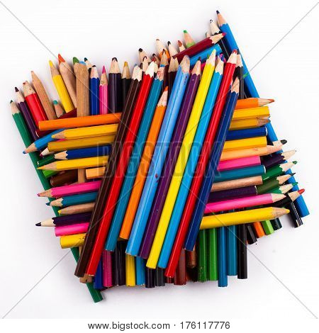 Top view of many colored pencils arranged in a pile on top of each other isolated on white background