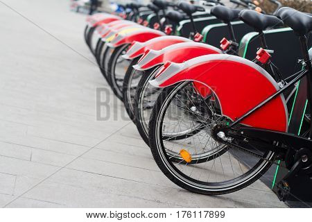 horizontal perspective view of city bike stand with row of red bicycles for rent on a city street selective focus
