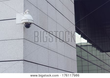 horizontal front view of white surveillance camera on business building marble wall in the city