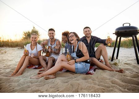 Young company of friends rejoicing, smiling, playing guitar, resting at beach at sunrise.