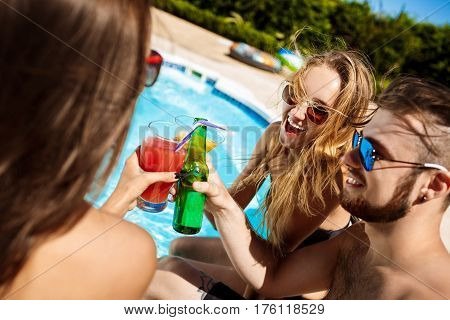 Young friends speaking, smiling, drinking cocktails, resting, relaxing near swimming pool. Copy space