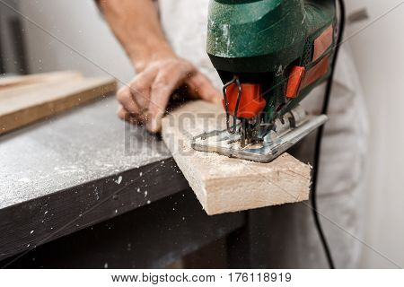 Close up photo of cutting wood with fretsaw over white background. Copy space.