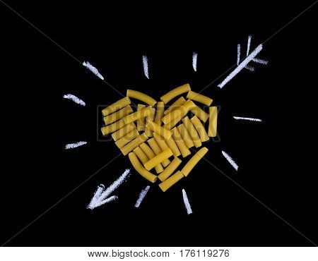Heart shape made of pasta tortiglioni. Pasta in the shape of a heart on a black background. I love pasta.
