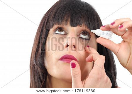 a closeup view of woman applying eye drop