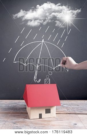 Umbrella being sketched on a chalkboard protecting a house