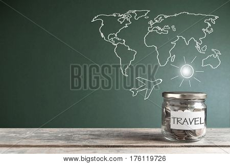 Travel savings jar by a chalkboard with a world map