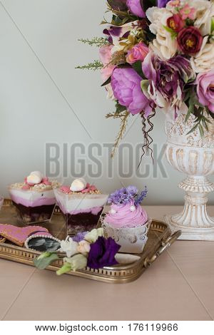Wedding decorations. Bouquets of flowers and cake on the chest of drawers