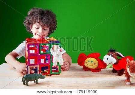 The beautiful smiling kid in a white t-shirt checks construction of the house. Friends together build the house. On a green background.