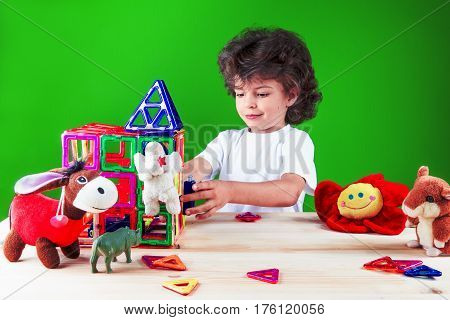 Cute curly boy in a white t-shirt is building a wall of a house with friends. Toys help to build a house. On a green background.
