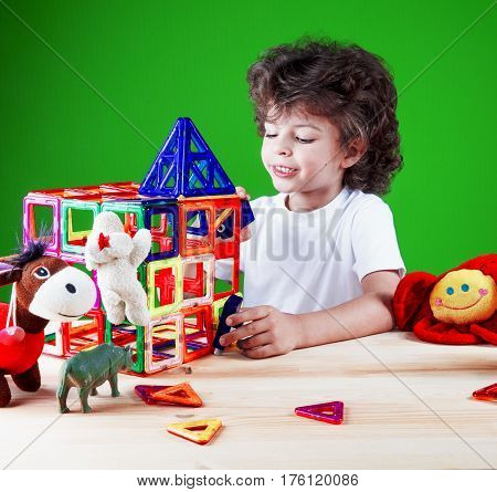 Little cute boy inventor closeup in a white t-shirt builds a house with his friends toys. Toys help to build the house. On a green background.