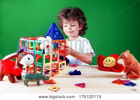 Happy brown-eyed boy close up in white t-shirt is building a business center under the supervision of their friends toys. Toys help to build the house. On a green background.