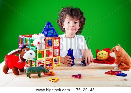 Happy smart brown-eyed boy close up in white t-shirt is building a business center together with their toys. Toys help to build the house. On a green background.