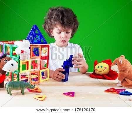 Brooding brown-eyed boy close up in white t-shirt is building a business center together with their toys. Toys help to build the house. On a green background.