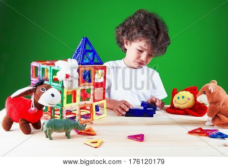 Crying brooding brown-eyed boy close up in white t-shirt looks like his friends are the toys break built house. On a green background.
