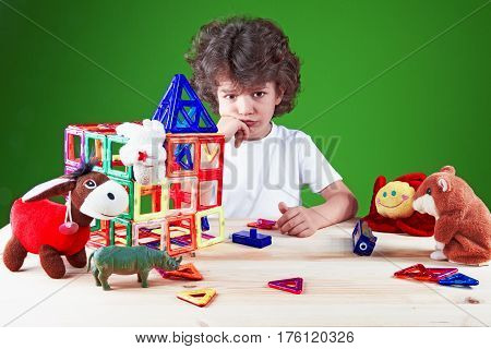 Sad brooding brown-eyed boy close up in white t-shirt looking at the camera. Near built home surrounded by toys.The construction of the house. Toys help to build the house. On a green background.