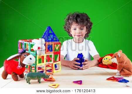 Smiling brown-eyed boy close up in white t-shirt looking at the camera. Near built home surrounded by toys.The construction of the house. Toys help to build the house. On a green background.