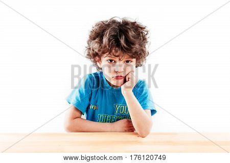 Cute curly boy propping his head and sticking out his lips thoughtfully looking at the camera. Sitting at a wooden table. On a gray background.