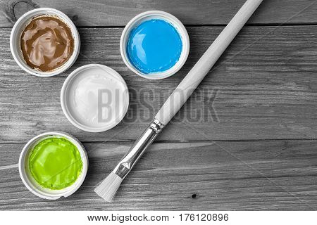 Brush and colorful paint in jars on an old wooden background with copy space in black and white tones