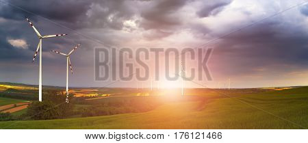 Wind turbines under cloudy sky. Wind power plant at the sunset. Bright sun illuminate white wind turbines. Beautiful energy saver background.