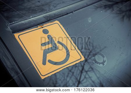 Disabled sign on the car glass. Macro shot.