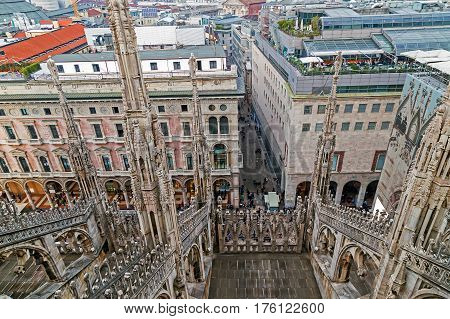 MILAN ITALY - DECEMBER 11 2016: View over Milan and street from the top of the gothic Milan Cathedral Italy. Church's roof statues in the foreground buildings of the city in the background.