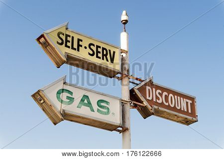 Vintage discount self serve gas sign arrows against sky