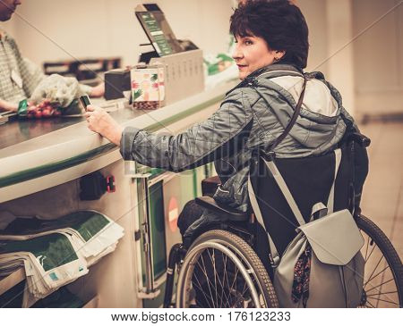 Disabled woman in a wheelchair in a store