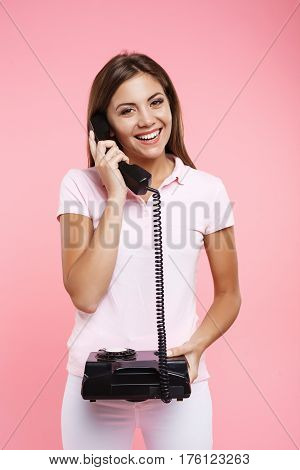 Portrait of beautiful woman in pink polo making phonecalls, with old balck landline, looking straight