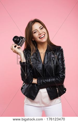Closeup portait of laughing fashion photographer in trendy outfut holding old roll-film camera looking